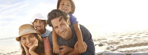 Eine Familie im Sommer am Strand, für die regelmäßiges Puls messen wichtig ist.