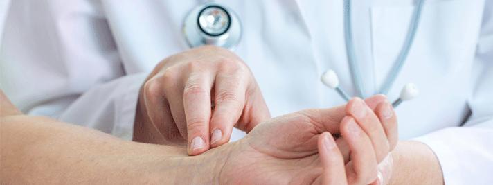 Ein Arzt, der den Puls am Handgelenk mit zwei oder drei Fingern misst.