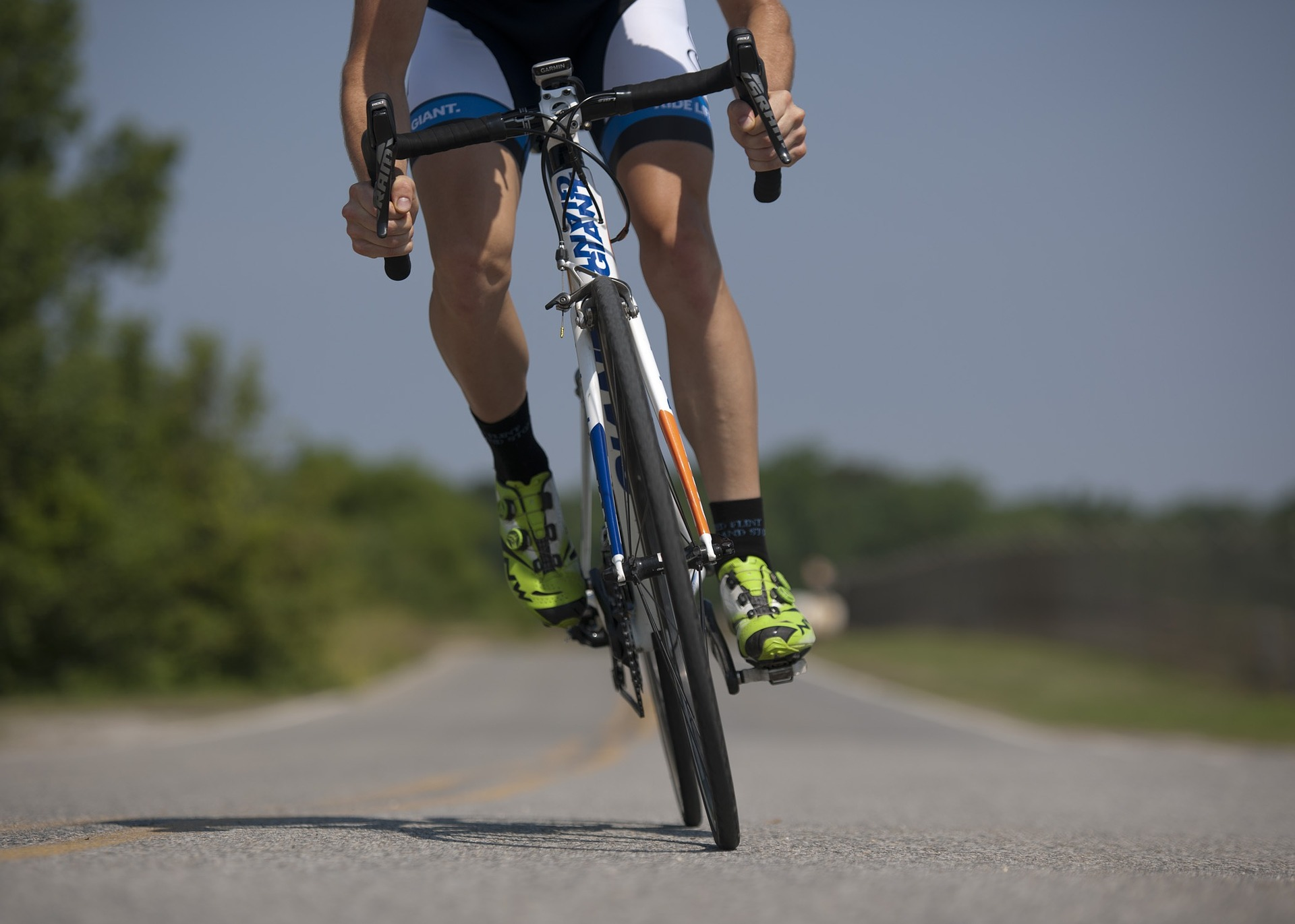 Fahrradfahrer macht Sport und fährt auf der Straße. Er misst seinen Puls während des Trainings.