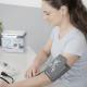Das Bild zeigt eine Frau beim Blutdruck messen mit einem Oberarm-Blutdruckmessgerät.
