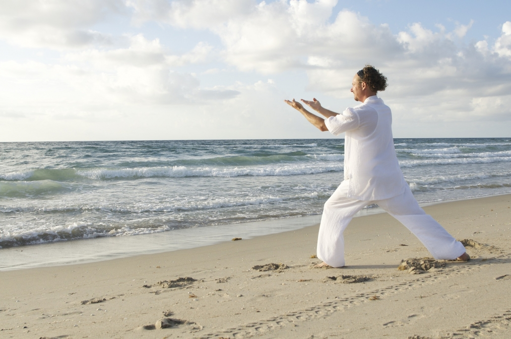 Mann macht Qi gong am Strand.